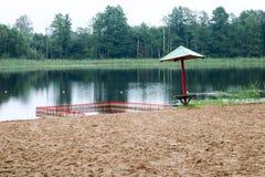 Samotny, zwisający zapadnięty parasol, i fechtunek, kojec dla kąpać się dzieci na piaskowatej plaży na brzeg jezioro, rzeka przy  obraz royalty free