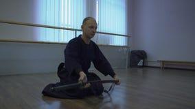 Samouraïs s'asseyant sur le plancher et transmettant à son épée du ` s de katana, conduisant le rituel de kendo banque de vidéos