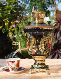 Samovar. Beautiful samovar on a white tablecloth on the background of summer flowers Royalty Free Stock Image