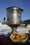 Samovar with cakes. Boiling samovar in a snowy field lit by the sun and a basket of cakes Stock Image