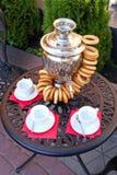 Samovar con los panecillos y la taza en la tabla Té de tarde fotos de archivo