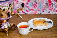 Samovar con una empanada de la taza y de los pescados Imágenes de archivo libres de regalías