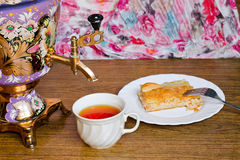 Samovar with a cup and  fish pie. Vintage Russian samovar with a great cup of tea on a wooden background royalty free stock images