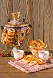 Samovar en un fondo de madera con los panecillos y el té Fotografía de archivo