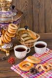 Samovar en un fondo de madera con los panecillos y el té Fotos de archivo libres de regalías