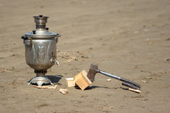 Samovar and a hatchet. On the wet sand Royalty Free Stock Photo