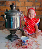 Samovar and little girl smiling. Little girl in a red polka-dot dress, with a samovar, sitting in front of a brick wall and smiling.Water is poured from a Royalty Free Stock Image