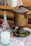 Samovar and moonshine bottle on a lace tablecloth. Rustic still life in traditional Russian style stock image