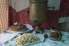 Samovar och bröd för tappning som rysk är salta på tabellen som täckas med en bordduk Välkomnande till Ryssland Från Ryssland med Royaltyfria Bilder