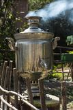 The samovar stands on a stump in the garden. Royalty Free Stock Image
