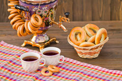 Samovar Tea cup and donut on a napkin in a cage. Vintage Russian samovar with a great cup of tea on a wooden background royalty free stock image