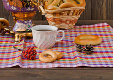 Samovar Tea cup and donut on a napkin in a cage. Vintage Russian samovar with a great cup of tea on a wooden background stock photography