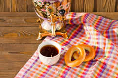 Samovar Tea cup and donut on a napkin in a cage. Vintage Russian samovar with a great cup of tea on a wooden background stock image