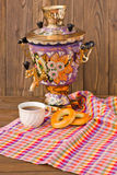 Samovar Tea cup and donut on a napkin in a cage. Vintage Russian samovar with a great cup of tea on a wooden background royalty free stock photography