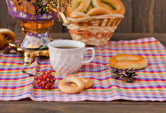 Samovar Tea cup and donut on a napkin in a cage. Vintage Russian samovar with a great cup of tea on a wooden background stock photos