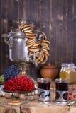 Samovar tradicional da chaleira do russo na tabela de madeira Chá preto, bagels, samovar vermelho do viburnum, do doce e do russo Fotos de Stock