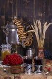 Samovar tradicional da chaleira do russo na tabela de madeira Chá preto, bagels, samovar vermelho do viburnum, do doce e do russo Imagem de Stock