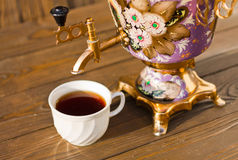 Samovar and two cups of tea on a wooden background. Vintage Russian samovar with a great cup of tea on a wooden background stock photos