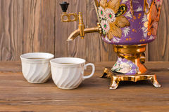 Samovar and two cups of tea on a wooden background. Vintage Russian samovar with a great cup of tea on a wooden background royalty free stock photo