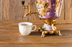 Samovar and two cups of tea on a wooden background. Vintage Russian samovar with a great cup of tea on a wooden background stock images