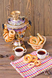 Samovar on a wooden background with bagels and tea. Vintage Russian samovar with a great cup of tea on a wooden background royalty free stock photo