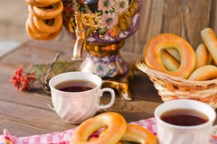 Samovar on a wooden background with bagels and tea. Vintage Russian samovar with a great cup of tea on a wooden background stock images