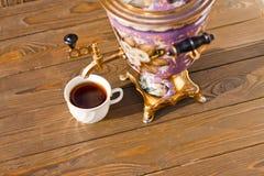 Samovar y dos tazas de té en un fondo de madera Fotografía de archivo libre de regalías