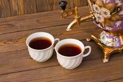Samovar y dos tazas de té en un fondo de madera Fotos de archivo libres de regalías