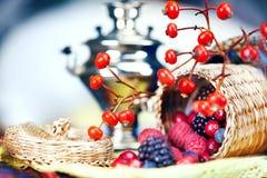 Samovar y una cesta con las bayas Foto de archivo libre de regalías