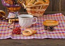 Samowar-Teeschale und -donut auf einer Serviette in einem Käfig Stockfotografie