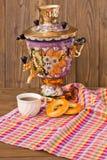 Samowar-Teeschale und -donut auf einer Serviette in einem Käfig Lizenzfreie Stockfotografie