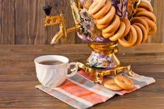 Samowar-Teeschale und -donut auf einer Serviette in einem Käfig Lizenzfreies Stockbild