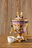 Samowar und zwei Tassen Tee auf einem hölzernen Hintergrund Stockfotografie