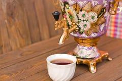 Samowar und zwei Tassen Tee auf einem hölzernen Hintergrund Stockbilder