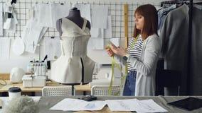 Samozatrudniający się kobieta krawczyna sprawdza z mądrze odziewający wzory przyczepiających dostosowywać atrapy wtedy bierze fot zdjęcie wideo