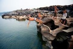 SAMPANBOK UBONRATCHATHANI - 2月26日:在湄公河的活动,游泳和演奏岩石的孩子钻孔石看法山姆 免版税库存照片
