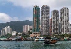 Sampanu prom przed wysokimi budynkami w schronieniu Hong Kong, Chiny zdjęcia stock