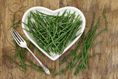 Samphire Health Food. Samphire vegetable health food on a heart shaped china plate and loose over old wood background Royalty Free Stock Images