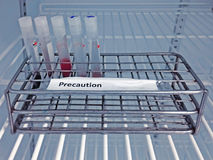 Sample blood collection tube with precaution label on rack. After analysis HIV infection screening test in refrigerator at laboratory hospital Stock Image