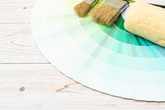 Sample colors catalogue pantone or colour swatches book. With paint roller brush royalty free stock photography