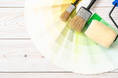 Sample colors catalogue pantone or colour swatches book. With paint roller brush royalty free stock image