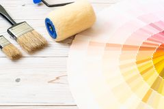 Sample colors catalogue pantone or colour swatches book. With paint roller brush stock photos