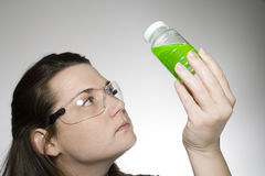 Sample examination 1. A laboratory technician is looking at a sample of green liquid Stock Image