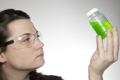 Sample examination 2. A laboratory technician is looking at a sample of green liquid Royalty Free Stock Images