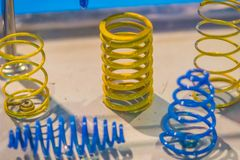 Sample product of blue and yellow metal helical coil springs. Sample product of blue and yellow metal helical coil springs of business stock photos