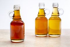 Sampler of pure maple syrup. Golden, amber and gold - three small glass bottles on a ceramic background stock image