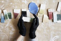 Samples of colored enamel for color ceramic in hands, working process in studio, clay, wood, craftю Stock Photography
