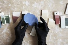 Samples of colored enamel for color ceramic in hands, working process in studio, clay, wood, craft. stock photo