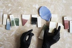 Samples of colored enamel for color ceramic in hands, working process in studio, clay, wood, craft. Royalty Free Stock Images