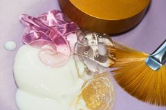 Samples of cosmetic creams with golden fan brush and cap on violet background Stock Images